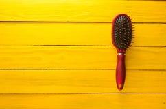 Trendig kvinnlig hårkam för håromsorg på en gul trätabell Trend av minimalism kopiera avstånd Top beskådar Royaltyfria Bilder