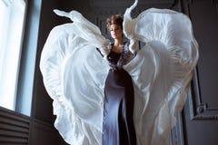 Trendig kvinnlig stående av den gulliga damen i klänning inomhus arkivbilder