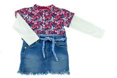 Trendig liten flickaskjorta med det blom- trycket och jeans arkivbild