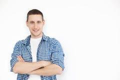 Trendig man som poserar på en vit bakgrund Korsad armstående med copyspace, tomt ställe av den glade mannen med borst i blått arkivfoton
