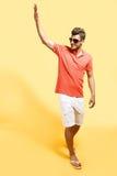Trendig man som saluterar att gå mot gul bakgrund arkivbilder