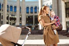 Trendig modern moder på en stadsgata med en pram. Barn mo Arkivfoto