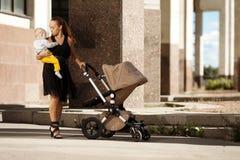 Trendig modern moder på en stadsgata med en pram. Barn mo Arkivbild