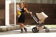 Trendig modern moder på en stadsgata med en pram. Barn mo Royaltyfria Bilder