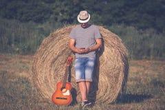 Trendig musiker med den akustiska gitarren som ser smartphonen Royaltyfria Foton