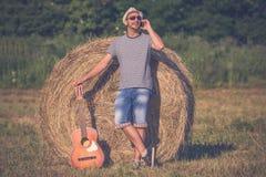 Trendig musiker med den akustiska gitarren som talar på smartphen Arkivfoto