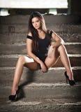 Trendig nätt ung kvinna med långa ben som sitter på gammal stentrappa Den härliga långa hårbrunetten på höga häl skor att posera Royaltyfri Foto