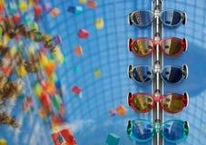 Trendig solglasögon av olika modeller på blå bakgrund arkivbilder
