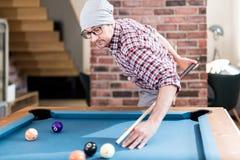 Trendig stads- man som siktar billiardbollen, genom att rymma pinnen bak hans baksida arkivfoto