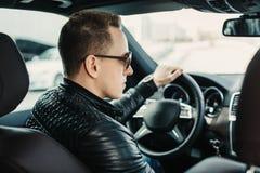 Trendig stilig man i solglasögon som sitter i hans lyx på Royaltyfria Bilder
