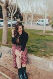 Trendig ung flicka som sitter på en bänk som shyly skrattar royaltyfri bild