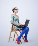 Trendig ung kvinna i klänningen och exponeringsglas som sitter på stol med en bärbar dator arkivfoton