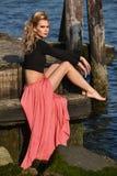 Trendig ung kvinna som bär den kantjusterade bästa och maxi kjolen som utomhus poserar på fartygmarina Arkivfoto