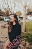 Trendig ung kvinna som sitter på en bänk som shyly ler royaltyfria bilder