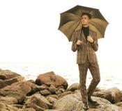 trendig ung man med paraplyet som st?r n?ra havet royaltyfria bilder