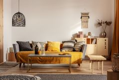 Trendig vardagsruminre med gul och grå design och lång kaffetabell i mitt royaltyfri fotografi