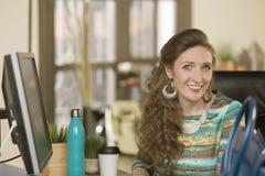 Trendig yrkesmässig kvinna i ett idérikt kontor Arkivfoton