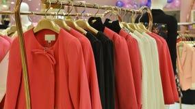 Trendiga kvinnor klär på hängare i kläder shoppar Arkivbild