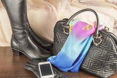 Trendiga kvinnors kängor, handväska från läder och mobil arkivfoton