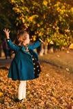 Trendiga liten flickalekar med höstsidor lyckligt barn utomhus Höstungemode Höstferier kopiera avstånd härligt arkivfoto