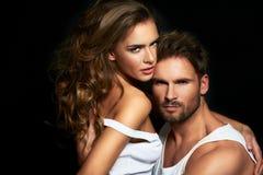 Trendiga par som poserar på studion Fotografering för Bildbyråer