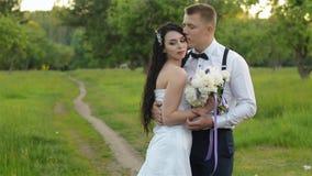 Trendiga unga brölloppar tycker sig om i en parkera eller ett trädgårdanseende på vägen i aftonen stilfullt stock video
