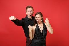 Trendiga unga par i den svarta kläderskjortaklänningen som firar födelsedagferiepartiet på ljust rött arkivfoton