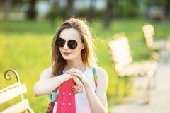 Trendigt blont flickasammanträde på en bänk i en stad parkerar Fotografering för Bildbyråer