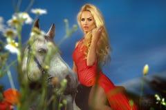 Trendigt foto av den attraktiva blonda flickan som rider en häst. Royaltyfri Foto