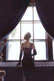 Trendigt foto för konst av den härliga flickan som blir på fönstret tillbaka sikt royaltyfri fotografi