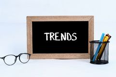 Trends concept written on blackboard for business with glasses, marker and pen case stock photo