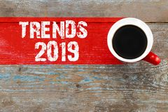 Trends 2019 / Cup of coffee with trends inscription on wooden ba stock image