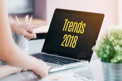 Trends 2018 on laptop screen with business people meeting in fro. Nt of computer screen on desk at office,Digital marketing concept Stock Image