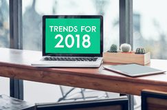 Trends for 2018 word in laptop computer screen with tablet on wo. Od stood table in at window with blur background,Digital Business or marketing trending Stock Image