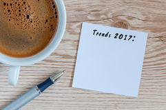 Trends 2017 written at notepad on table workplace near cup of morning coffee. New year business and fashion trendings stock photos