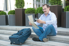 Trendy adult man in the town with touristic map outdoors. Royalty Free Stock Images