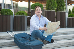 Trendy adult man in the town with touristic map outdoors. Royalty Free Stock Photography
