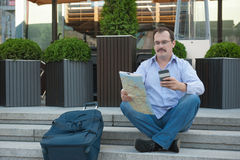 Trendy adult man in the town with touristic map outdoors. Stock Images