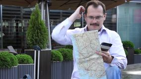 Trendy adult man in the town with touristic map outdoors. Trendy adult man in the town with mobile phone and touristic map outdoors stock video footage