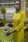 trendy african american girl watering tropical plants stock images