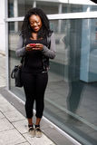 Trendy African woman reading a text message Stock Image