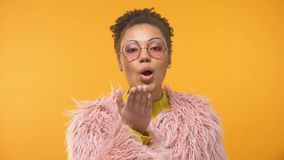 Trendy Afro-American lady in pink coat sending air kiss into camera, glamour