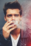 Trendy attractive man blowing smoke out of his mouth standing on grey background Stock Photo