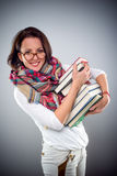 Trendy attractive woman carrying a pile of books Stock Images
