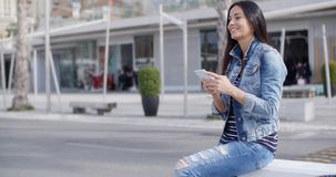 Trendy attractive young woman in a denim outfit. Perching on a wall on an urban promenade talking on her mobile and smiling at the camera stock footage