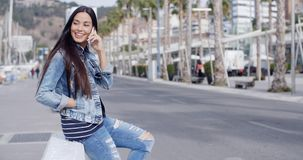 Trendy attractive young woman in a denim outfit. Perching on a wall on an urban promenade talking on her mobile and smiling at the camera stock video