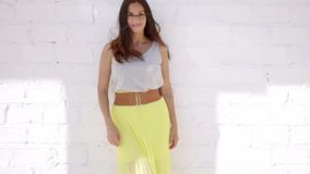 Trendy attractive young woman in a summer skirt. Trendy attractive young woman in a long colorful yellow summer skirt and white top standing against a white stock footage