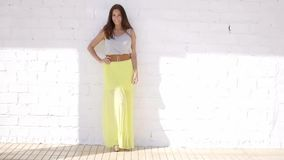 Trendy attractive young woman in a summer skirt. Trendy attractive young woman in a long colorful yellow summer skirt and white top standing against a white stock video