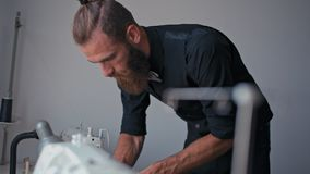 Trendy bearded man in black is working in his sewing fashionable clothing studio. Trendy bearded man in black is working in his sewing fashionable clothing stock video footage