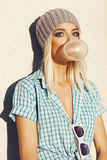 Trendy beautiful blonde model and Blow bubblegum. Trendy beautiful blonde  in grey knit hat and  blue shirt . Blow bubblegum. Outdoors, lifestyle Stock Photos